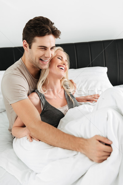 Happy lady smiling while lying in bed with her man Stock photo © deandrobot