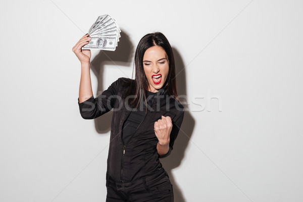 Happy woman with red lips holding money make winner gesture. Stock photo © deandrobot