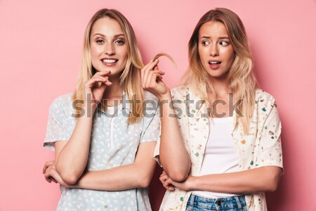 Two worried smiling women in dresses praying with crossed fingers Stock photo © deandrobot