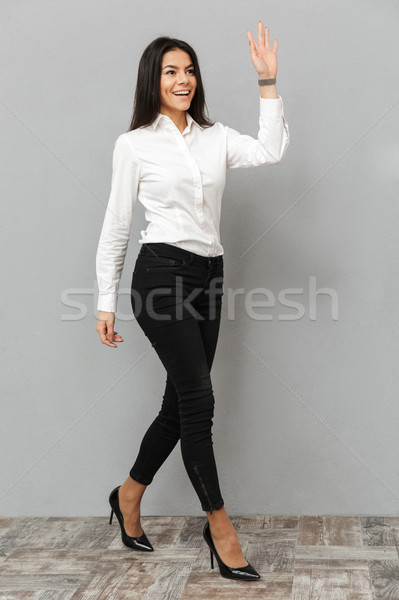 Full length image of happy businesswoman in white shirt and blac Stock photo © deandrobot