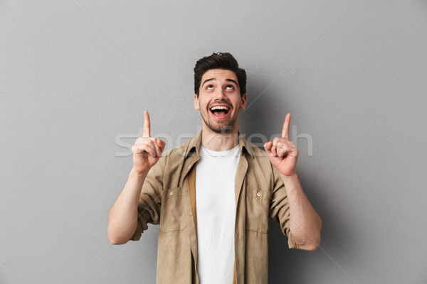 Stock photo: Portrait of a cheerful young casual man pointing up