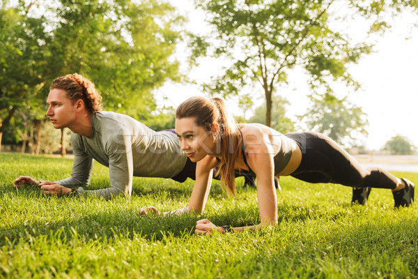 Photo of young caucasian sporty man and woman 20s in tracksuits, Stock photo © deandrobot