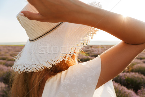Photo of beautiful young woman wearing straw hat smiling, and wa Stock photo © deandrobot