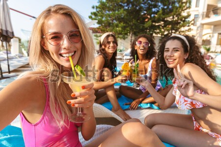 Image of four excited young women in swimwear Stock photo © deandrobot