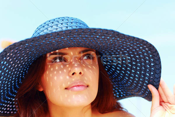 Closeup portrait of a beautiful woman in hat looking up Stock photo © deandrobot