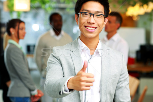Businessman giving thumb up to camera in front of colleagues Stock photo © deandrobot