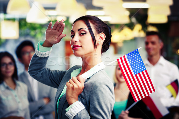 Patriotic businesswoman standing with USA flag in front of colleagues Stock photo © deandrobot