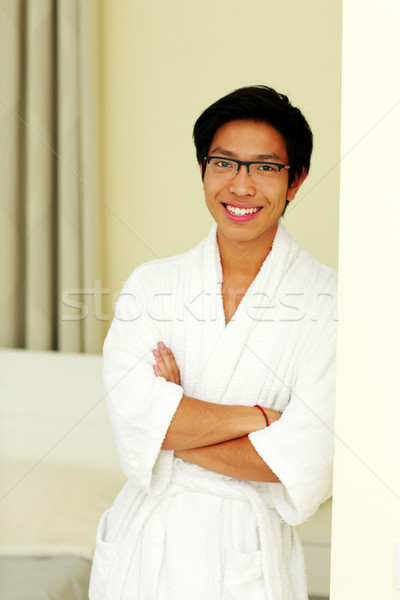 Happy asian man in bathrobe standing with arms folded at home Stock photo © deandrobot