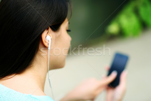 Closeup portrait of a woman in headphones listening to music with her smartphone Stock photo © deandrobot