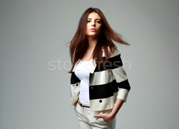 Portrait of a young beautiful woman in casual clothes on gray background Stock photo © deandrobot