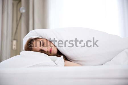 A young woman sleeping under a blanket Stock photo © deandrobot
