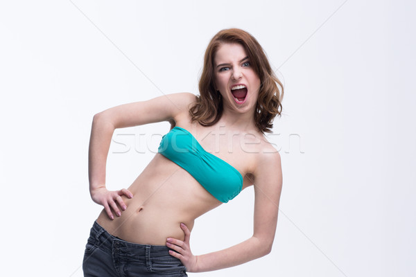 Young beautiful woman screaming over gray background Stock photo © deandrobot