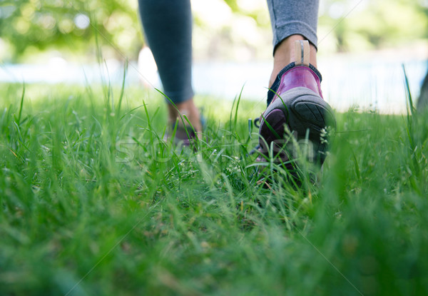 Footwear on female feet running on green grass Stock photo © deandrobot