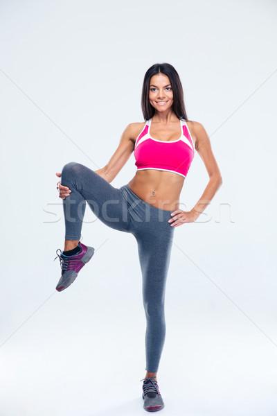 Smiling sporty woman stretching leg Stock photo © deandrobot