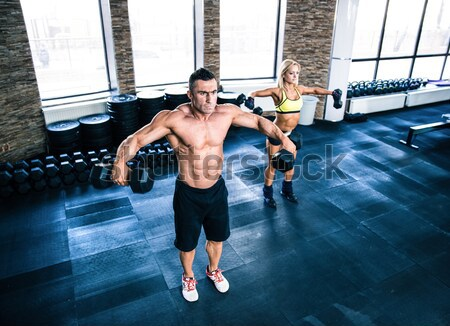 Woman workout with barbell and trainer Stock photo © deandrobot