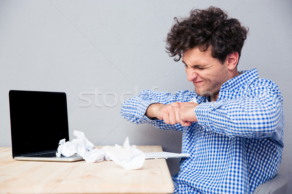 Businessman with laptop and crumpled papers Stock photo © deandrobot