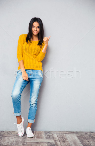 Trendy smiling woman showing finger right  Stock photo © deandrobot