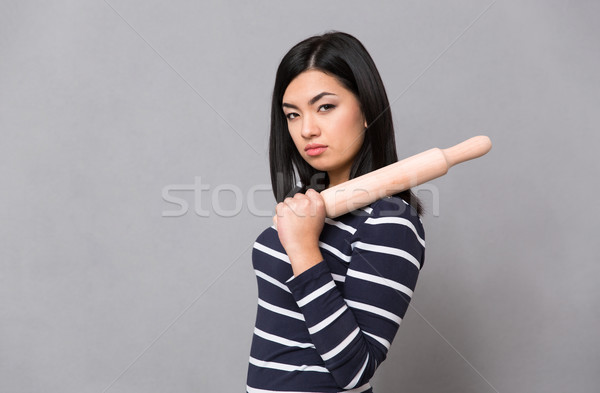 Asian girl holding rolling pin Stock photo © deandrobot