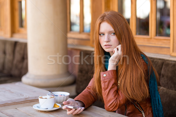 Woman using cellphone and waiting for somebody in outdoor cafe Stock photo © deandrobot