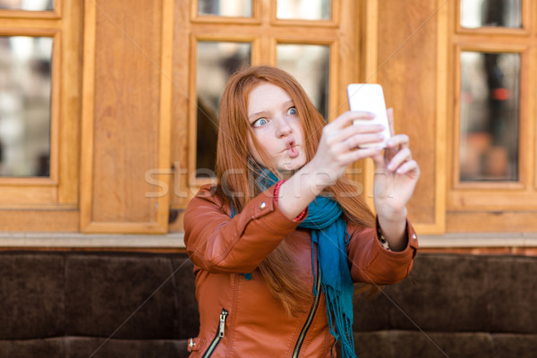 Amusing girl making funny faces and taking photos of herself  Stock photo © deandrobot