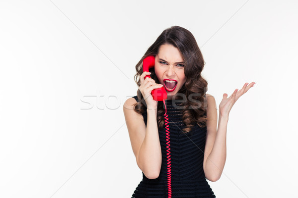 Hysterical aggressive young female shouting and talking on red telephone  Stock photo © deandrobot