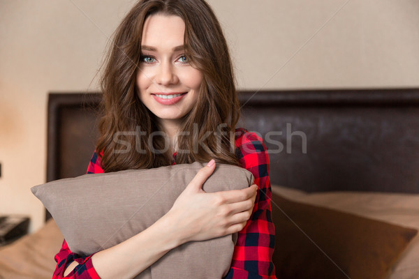 Smiling woman sitting on the bed with pillow  Stock photo © deandrobot