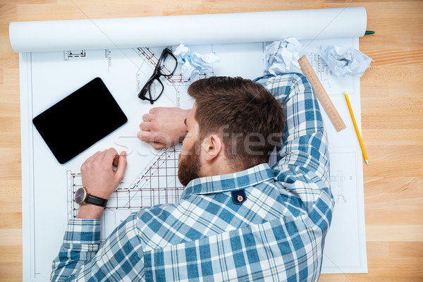 Exhausted bearded young architect sleeping on workplace  Stock photo © deandrobot