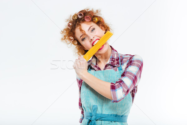 Pretty housewife standing and posing with uncooked spagetti Stock photo © deandrobot