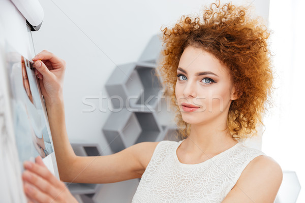 Smiling woman photographer put photos on whiteboard in office Stock photo © deandrobot