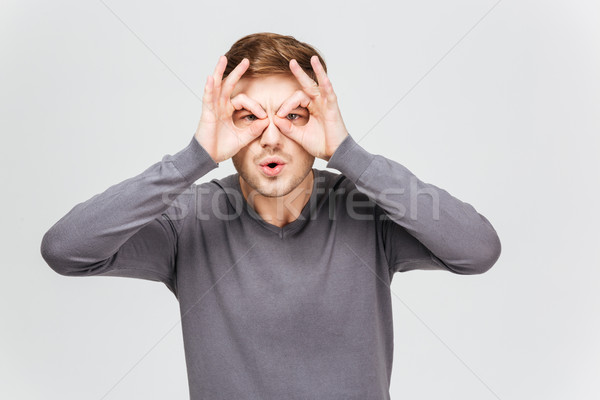 Funny young man in grey pullover making glasses with hands  Stock photo © deandrobot