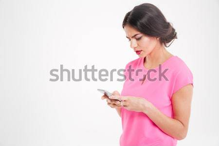 Unhappy frowning young woman using smartphone Stock photo © deandrobot