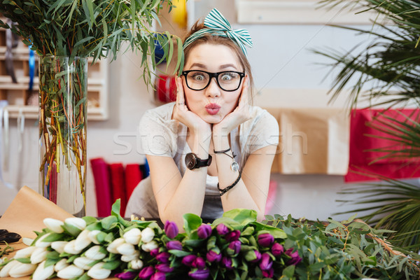 Amusing woman florist making funny face standing in flower shop Stock photo © deandrobot