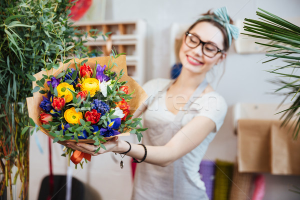 Cheerful woman florist showing bouquet of colorful flowers  Stock photo © deandrobot