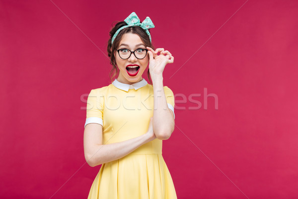 Happy attractive pinup girl in yellow dreass and glasses Stock photo © deandrobot