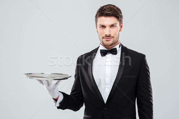 Portrait of young butler in tuxedo holding empty tray Stock photo © deandrobot