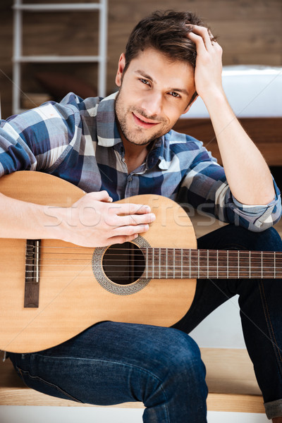 Attractive young man in checkered shirt with guitar Stock photo © deandrobot