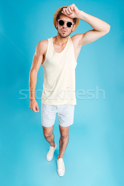 Full length of tired exhausted man in hat and sunglasses Stock photo © deandrobot