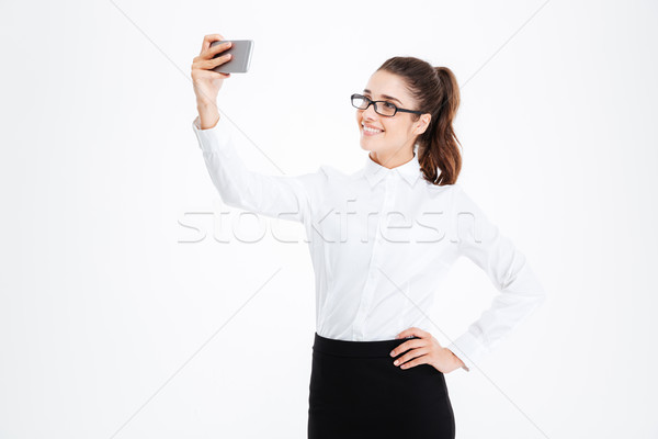 Smiling business woman in glasses making selfie using cell phone Stock photo © deandrobot