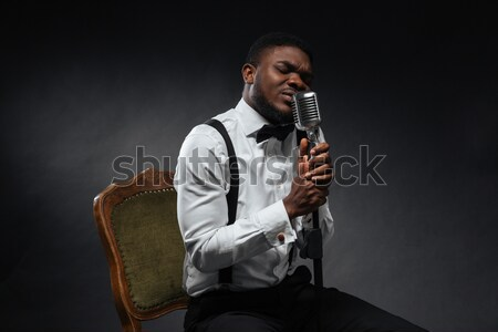 Afro american man singing into vintage microphone Stock photo © deandrobot