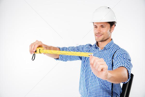 Happy young man building engineer in helmet using measuring tape Stock photo © deandrobot