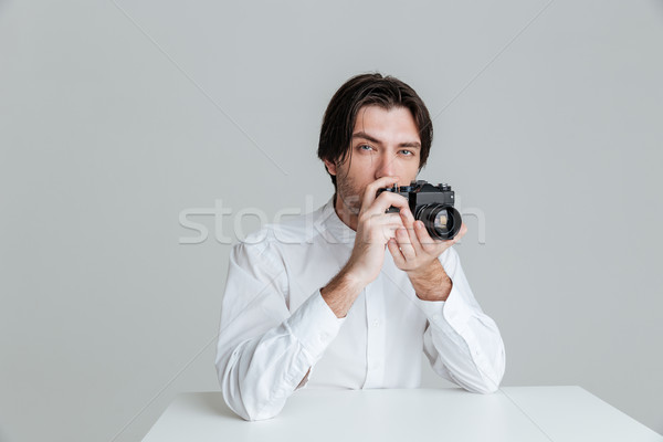 Man ready to make photo while sitting at the table Stock photo © deandrobot