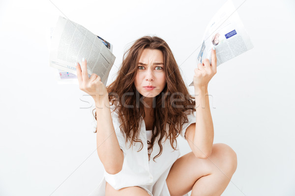 Irritated young brunette woman in casual wear holding newspapers Stock photo © deandrobot