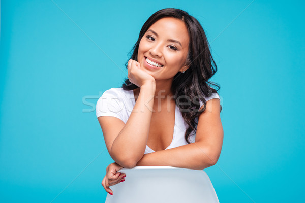 Cheerful young vietnamese woman sitting on the chair Stock photo © deandrobot