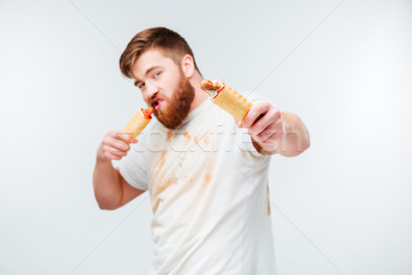 Hungry bearded man in dirty shirt eating two hotdogs Stock photo © deandrobot