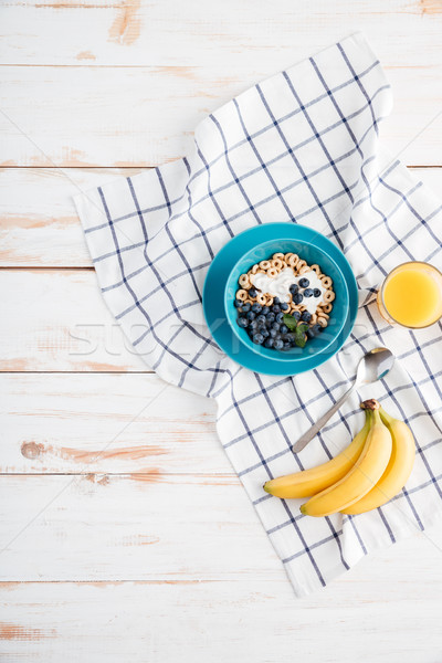 Oat cereals with berries and cream, cup of orange juice Stock photo © deandrobot