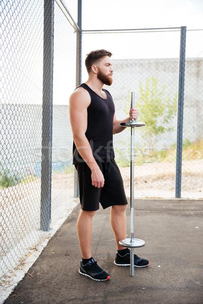 Full length portrait of a serious bearded sportsman holding barbell Stock photo © deandrobot