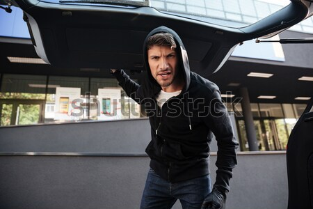 Criminal man threatening with gun and looking at car trunk Stock photo © deandrobot