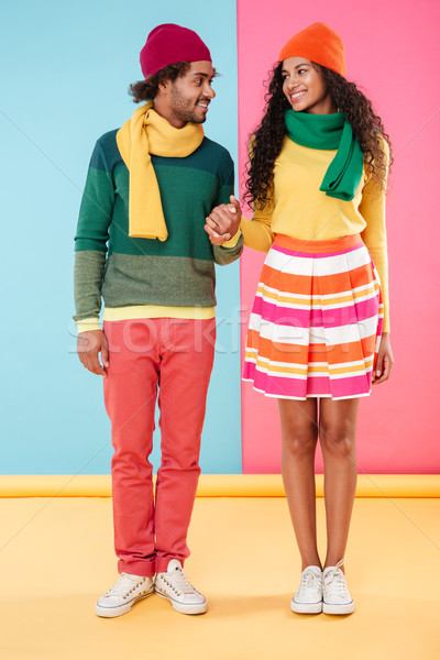 Happy african american young couple standing and holding hands Stock photo © deandrobot