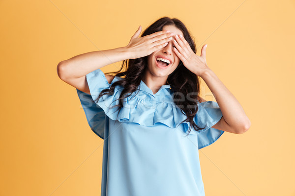 Portrait of a woman in blue dress covering her eyes Stock photo © deandrobot