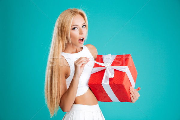 Happy amazed young woman opening red gift box Stock photo © deandrobot